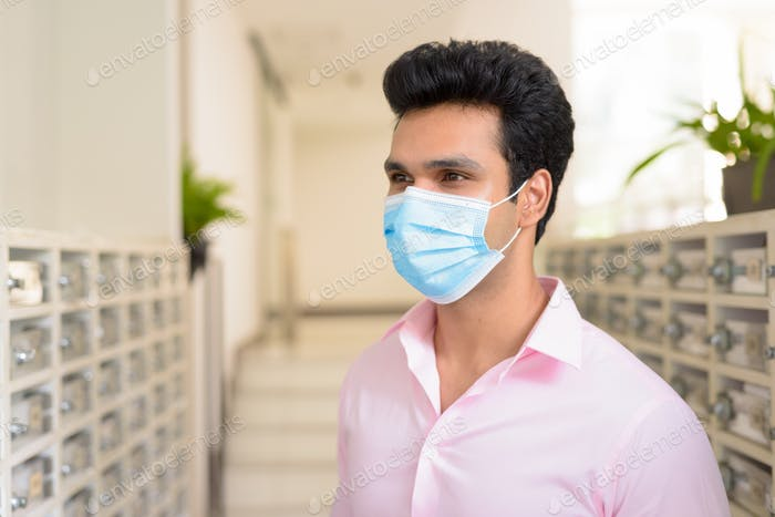 Face of young Indian businessman wearing mask while checking the mailbox