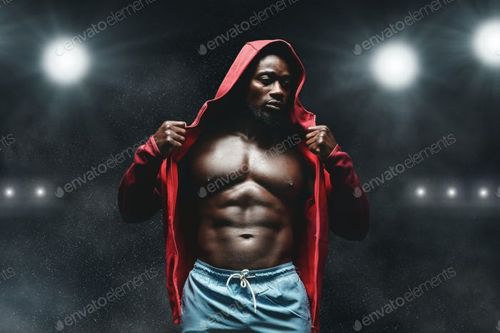 Afro fighter in hoodie at boxing ring