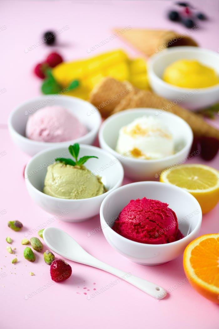 Ice cream balls in bowls, waffle cones, berries, orange, mango, lemon, mint, pistachio on pink