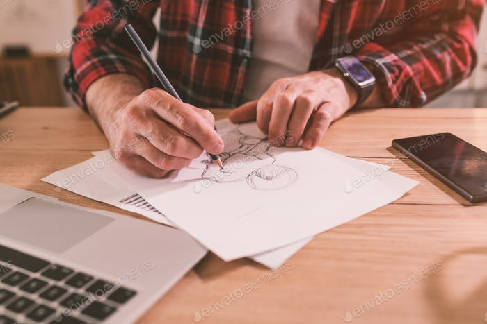 Illustrator freehand sketching motorcycle rider with pencil