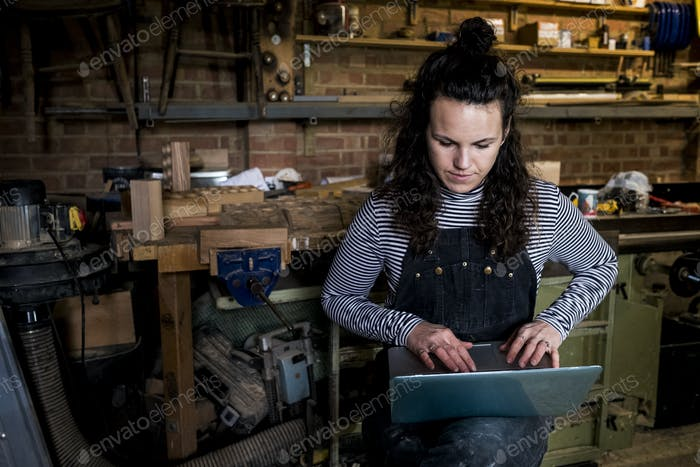 Woman with long brown hair wearing dungarees standing in wood workshop, typing on laptop computer.