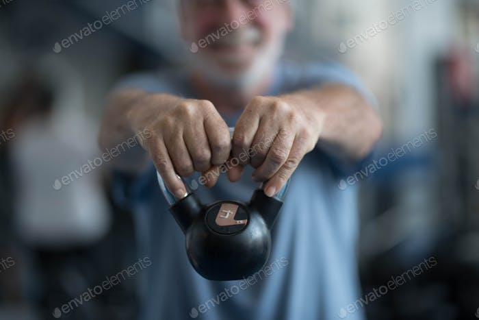one mature man holding a weight at the gym doing exercise to be healthy and fitness