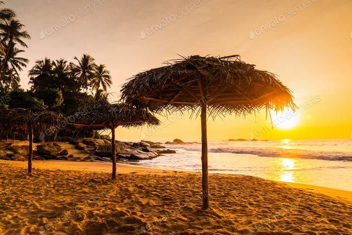 Two beach umbrellas at sunrise on a sandy beach. Tropical island