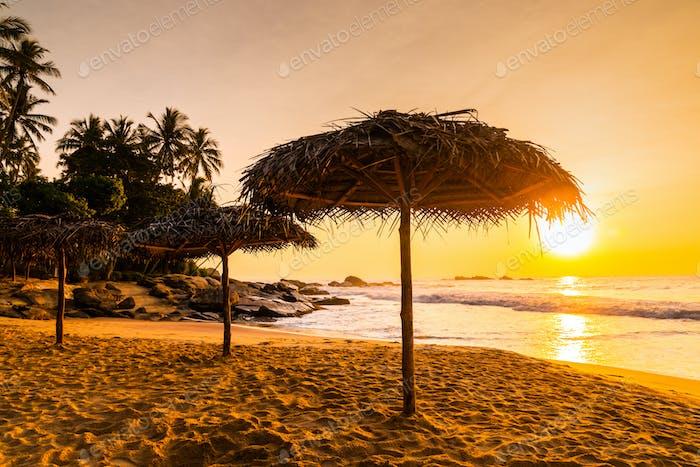 Two beach umbrellas at sunrise on a sandy beach. Tropical island
