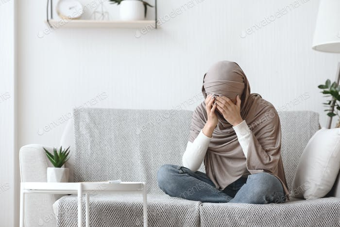 Upset muslim woman in headscarf crying on couch at home