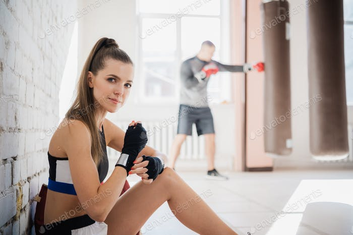 Девушка боксер на стене из белого кирпича обертывает спортивную повязку для бокса на руках