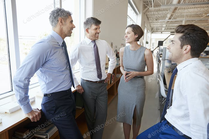 Corporate business colleagues talking in an open plan office
