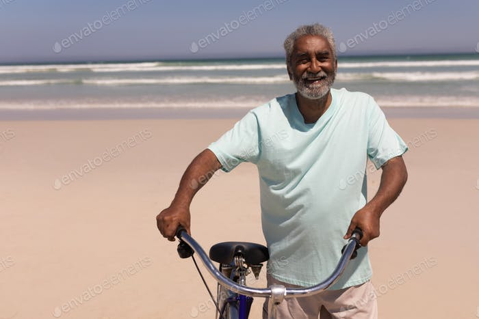 Front view of happy senior man with bicycle standing on beach in the sunshine