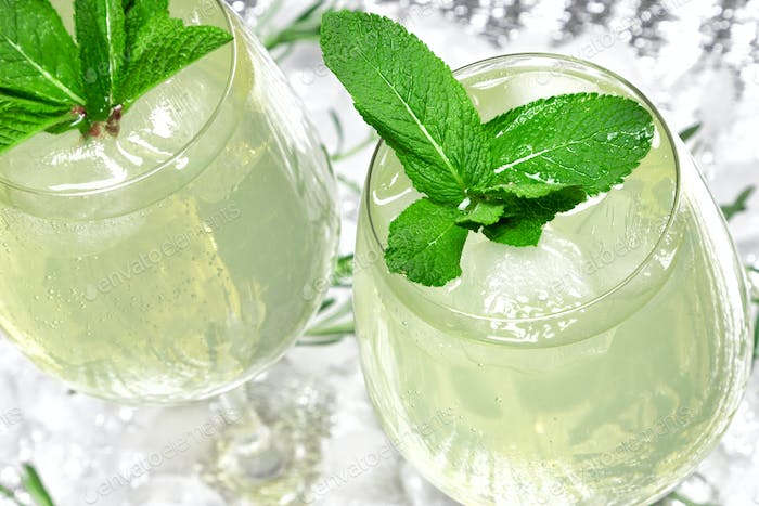 Refreshing summer drink with mint and ice cubes in wine glasses