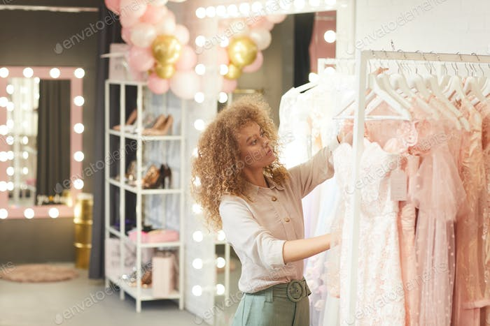 Young Woman Choosing Dresses in Clothing Boutique