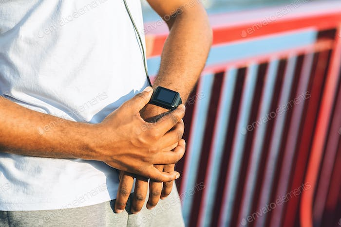 Hands of black guy checking heart rate on smartwatch