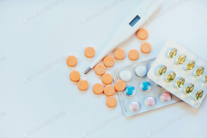 Flu. Thermometer with elevated temperature and many pills on light background