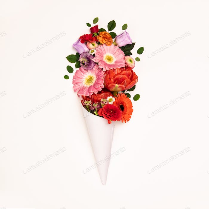 Bouquet of flowers in paper cone on a white background