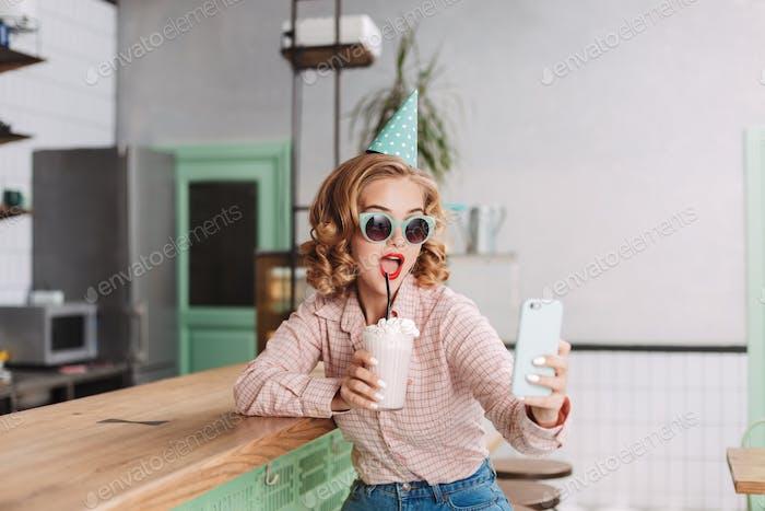 Schöne Dame in Geburtstagskappe sitzt an der Bar Theke mit Milchshake nehmen niedlich selfie in cafe