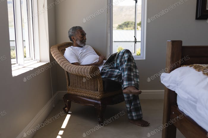 Senior man using digital tablet while sitting on a wicker chair in bedroom at home