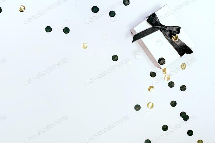 Weiße Geschenkbox mit schwarzem Band und Konfetti auf weißem Hintergrund.