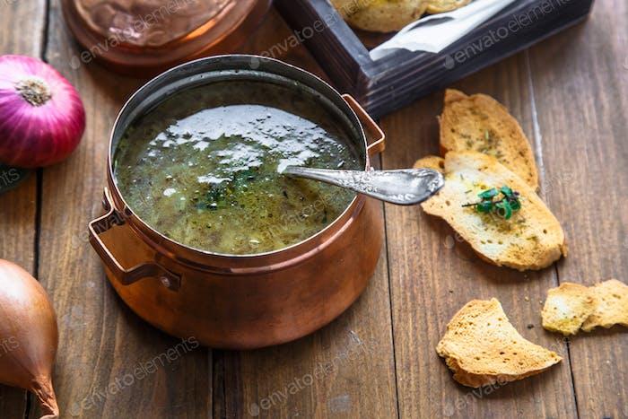 Blick auf Kupfertopf mit Zwiebelsuppe und Croutons