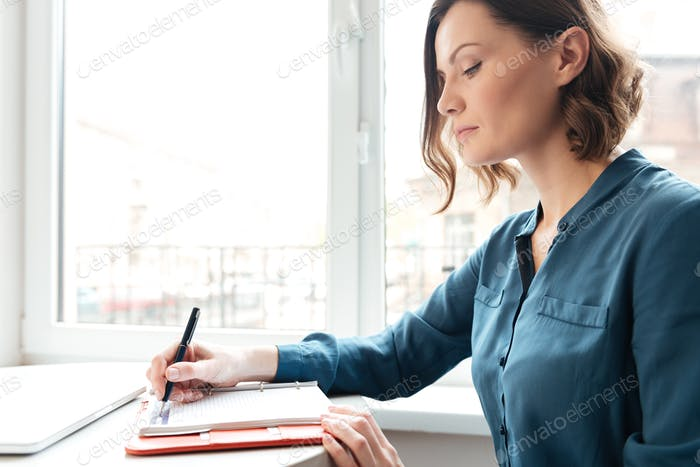 Side view of a woman making notes in her diary