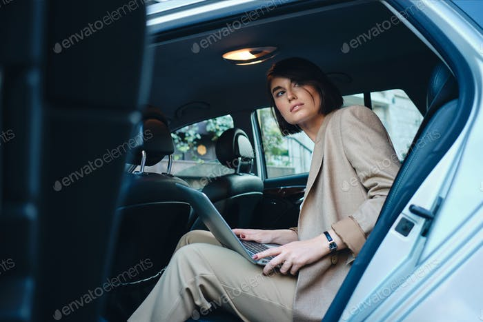Young beautiful stylish businesswoman thoughtfully looking away working on laptop in car
