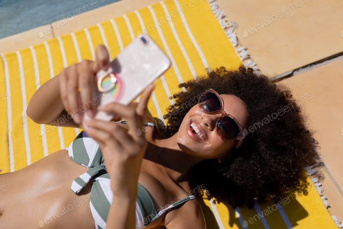 Young woman using mobile phone near swimming pool