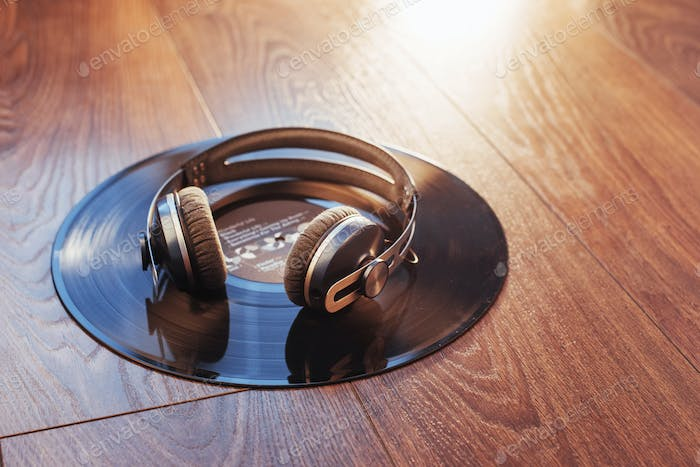 vinyl record and headphone over wooden table. Audio enthusiast,music lover or professional disc