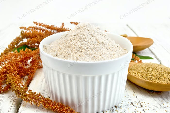 Flour amaranth in white bowl with spoon on board