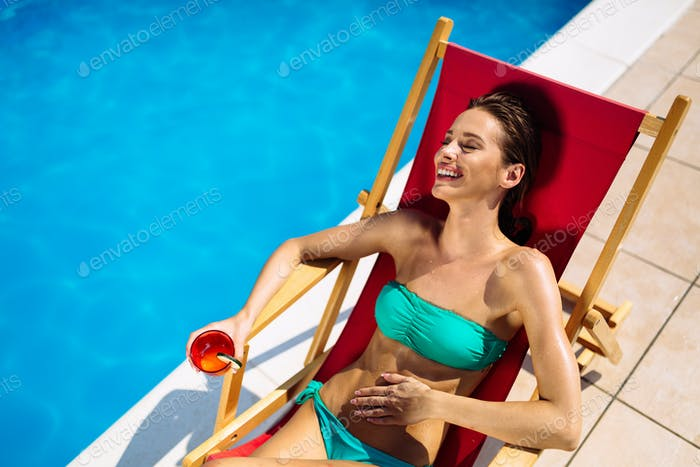Beautiful woman drinking cocktail and sunbathing at pool