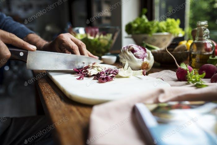 Closeup of hand with knife cutting fresh radicchio
