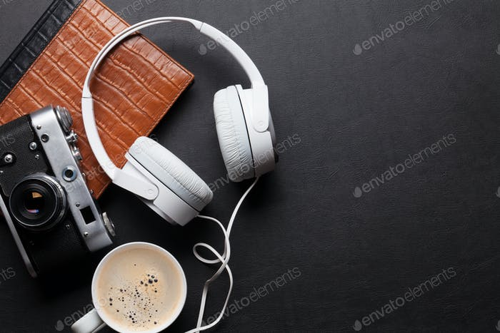 Office leather desk table with headphones, camera and coffee