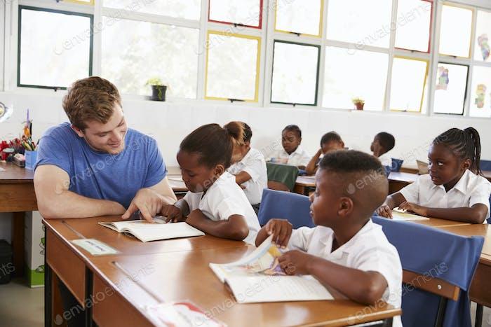 Freiwillige Lehrer helfen junge Mädchen an ihrem Schreibtisch in der Klasse