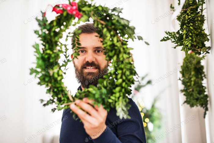 A hipster man holding and looking through a green wreath at Christmas time.