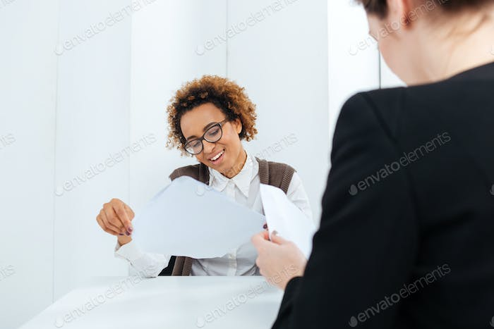 Smiling african american businesswoman having job interview and filling application
