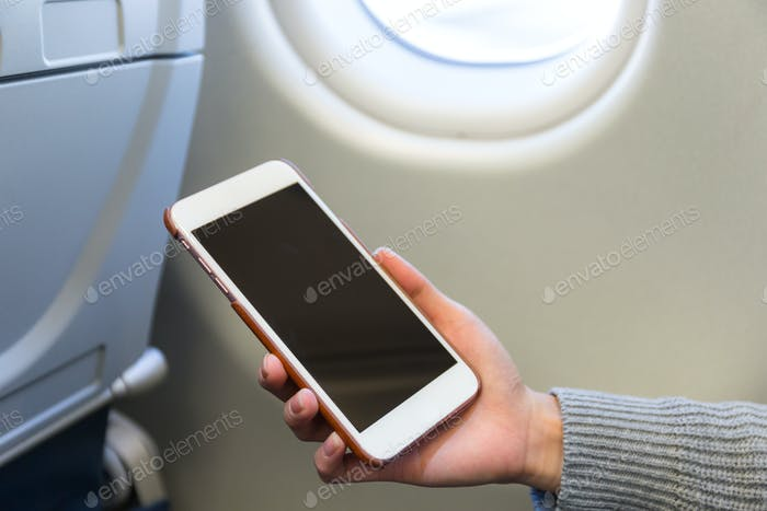 Woman use of cellphone inside air plane