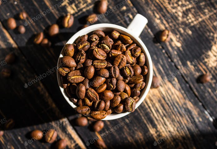 Cup with coffee beans at morning sunlight