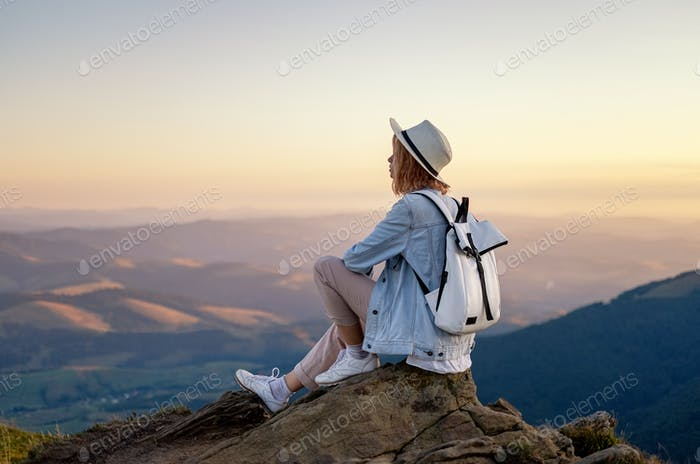 A girl with a backpack in the mountains. Tourism and adventure