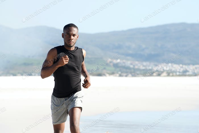 Healthy young african man running along the seashore