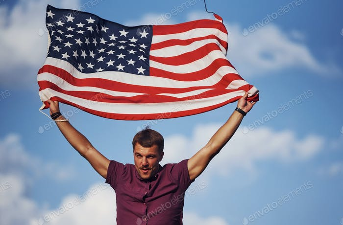 Patriotic happy man waving American Flag against cloudy blue sky