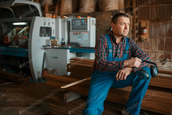 Joiner in uniform at his workplace on timber mill