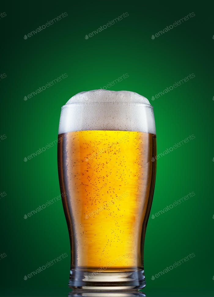Glass of light beer with foam on the green background