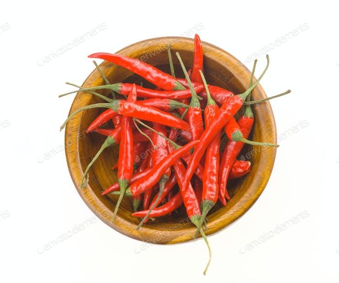 rote Chilis in Holzschale isoliert auf weiß