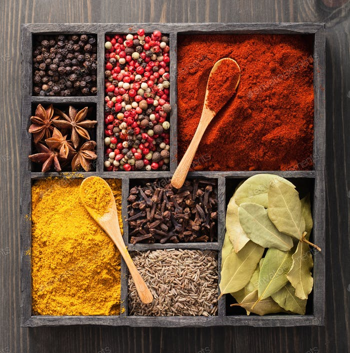 spices in box pink and black pepper, paprika powder, curry, bay