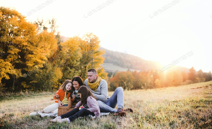 A young family with two small children having picnic in autumn nature at sunset
