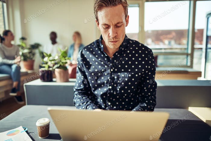 Focused young businessman sitting at his desk using a laptop