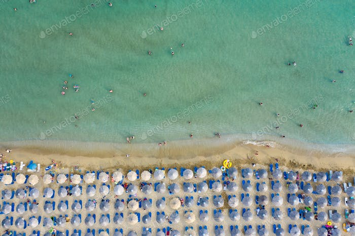 Aerial top view on the sandy beach. Umbrellas, sand and sea waves landscape.