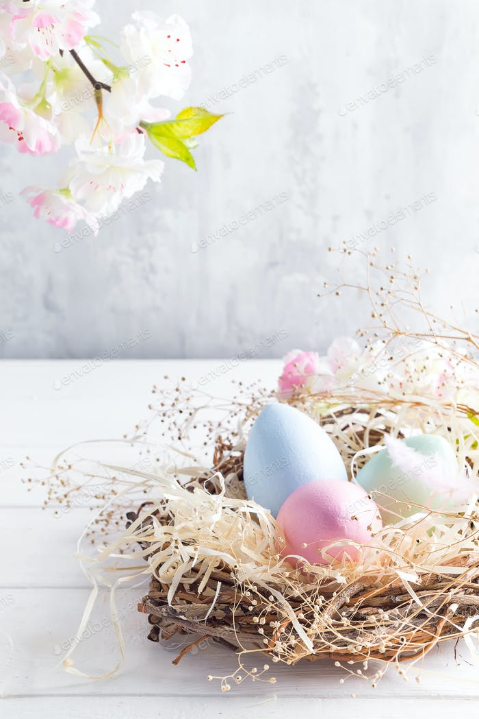 Beautiful flower with colorful eggs in nest on light background. Spring and Easter holiday concept