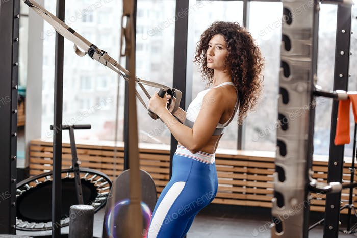 Athletic curly girl dressed in a sportswear has a TRX workout in the modern gym full of sun light