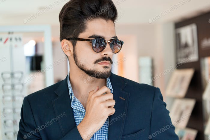 Handsome fashion young man posing in new sunglasses