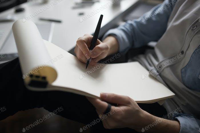 Designer hands drawing design project.