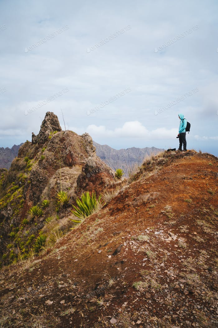 Traveler with backpack looking over the mountain peaks. Stunning arid landscape of Santo Antao