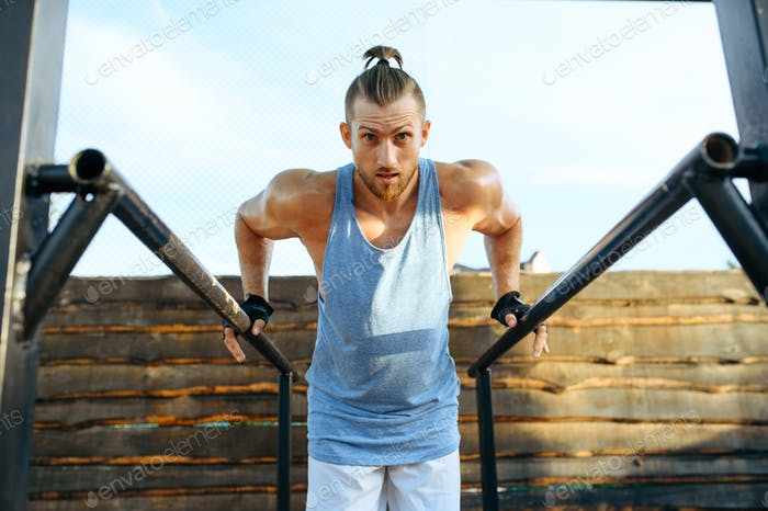 Man doing exercise on bars, street workout